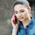 Closeup portrait young unhappy teen woman, talking on cell phone having unpleasant, bad conversation, outdoor. Negative emotions, depression